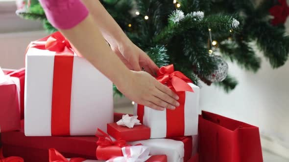 Thumbnail for Woman Putting Present Under Christmas Tree 1