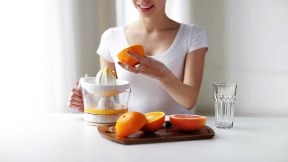 Woman With Squeezer Squeezing Orange Juice At Home 2