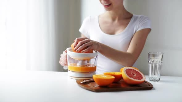 Woman With Squeezer Squeezing Orange Juice At Home 3
