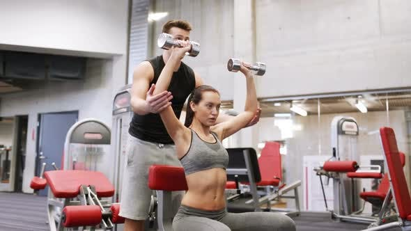 Thumbnail for Young Couple With Dumbbells Flexing Muscles In Gym