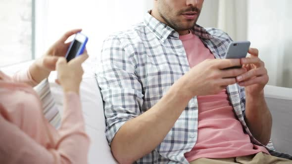 Cover Image for Couple With Smartphones Texting At Home 3