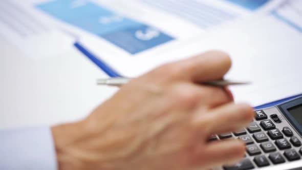 Thumbnail for Geschäftsmann Hand mit Taschenrechner und Papiere
