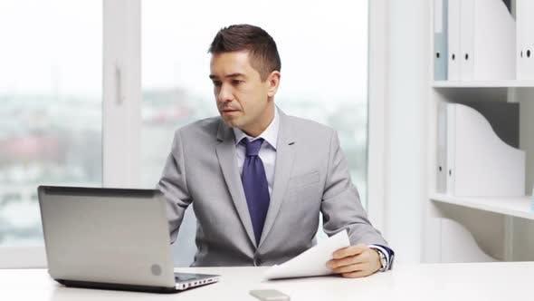 Thumbnail for Geschäftsmann mit Laptop und Papieren