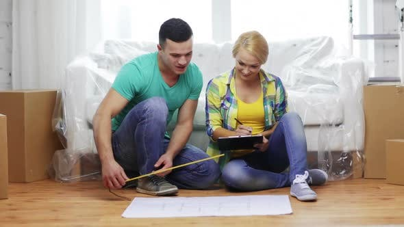 Thumbnail for Smiling Couple Looking At Blueprint In New Home 3