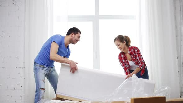 Thumbnail for Smiling Couple Opening Big Cardboard Box With Sofa