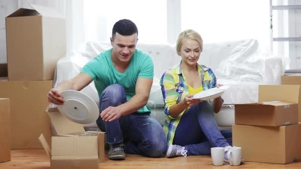 Thumbnail for Smiling Couple Unpacking Boxes With Kitchenware 1