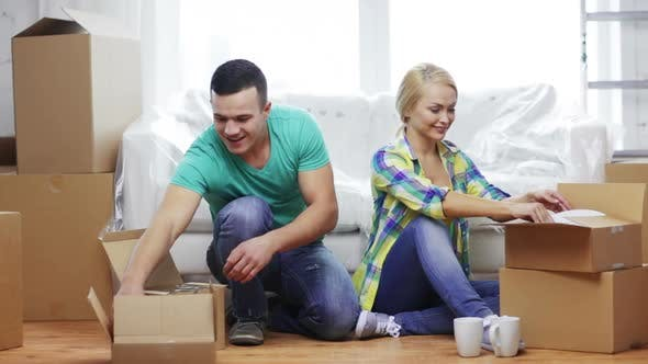 Thumbnail for Smiling Couple Unpacking Boxes With Kitchenware 2