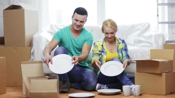 Thumbnail for Smiling Couple Unpacking Boxes With Kitchenware 3