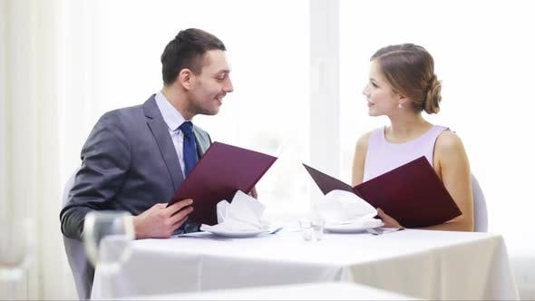 Thumbnail for Smiling Couple With Menus At Restaurant 1