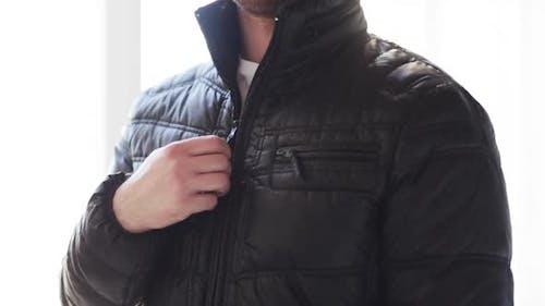 Close Up Of Man Unzipping His Black Jacket At Home 2