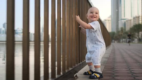 Laughing Boy at the Age of 1 Year Dancing Holding the Railing and Learning To Walk Making the First