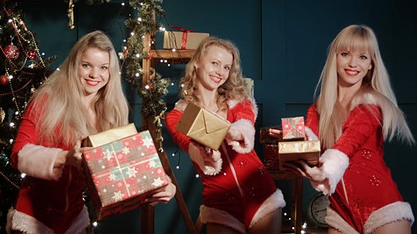 Thumbnail for Women in Santa Claus' Costumes With Christmas Gift