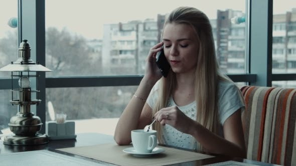 Thumbnail for The Girl Speaks By Phone In Cafe And Drink Tea