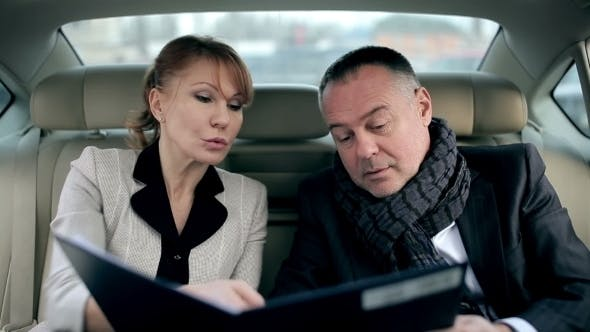 Thumbnail for Business Partners Discussing Document In The Car