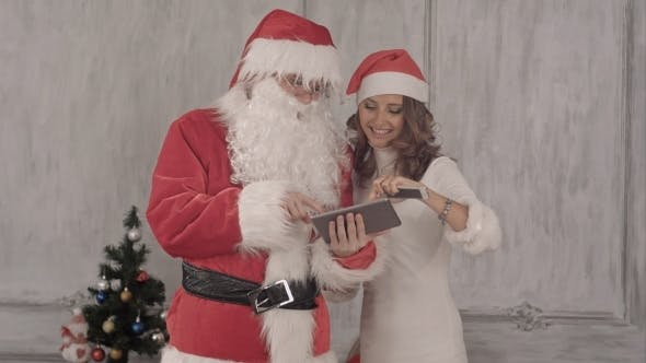Thumbnail for Loughing Santa And Beautiful Woman Use Tablet.