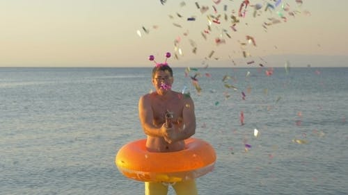 Man With Confetti Cracker At The Seaside