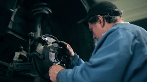 Mechanic Inspecting Car Brake Discs