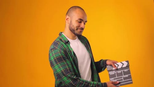 Casual Young African American Man Claps Clapperboard Against Yellow Background