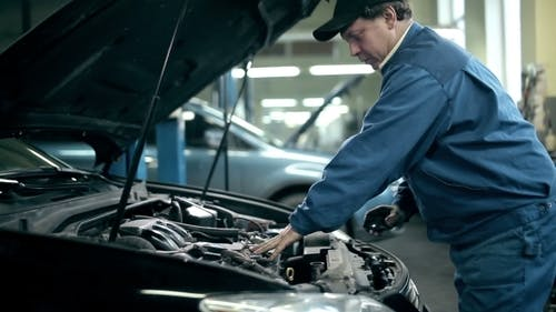 Serviceman Inspecting The Car Engine