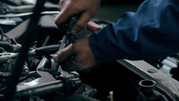 Serviceman Repairing Car Engine