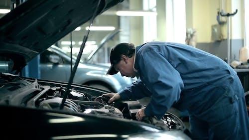 Mechanic Inspecting The Car Engine