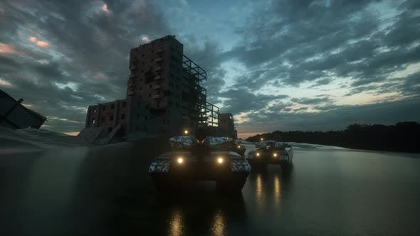 Group of Heavy Military Tanks Moving through street of destroyed city at sunset