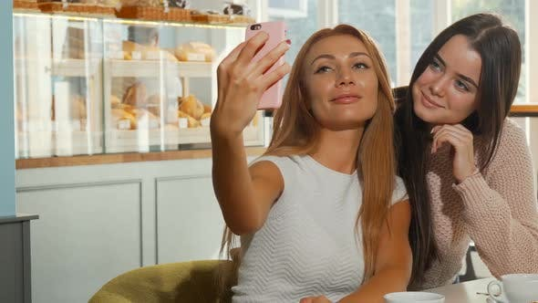 Thumbnail for Two Cheerful Young Women Taking Selfies at the Coffee Shop
