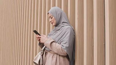 Arabic Woman Texting on Smartphone Outdoors