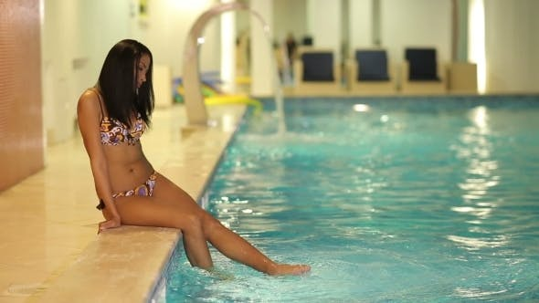 Young Woman Sitting Poolside