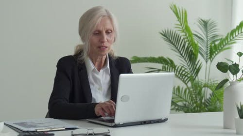 Happy Mature Woman Celebrates Online Victory with a Laptop While Sitting at Her Workplace in the