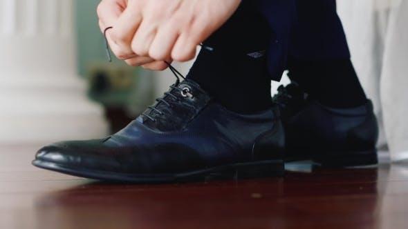 Thumbnail for Hände des Menschen gebunden an die Schuhspitze