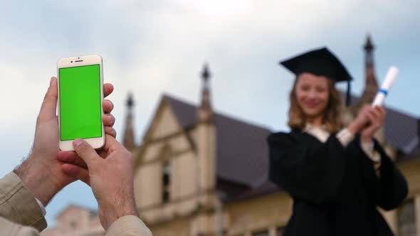 Thumbnail for A Photo on the Phone with Blank Screen of a Young Woman Who Has Just Received Her Master's Degree.
