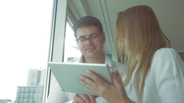 Thumbnail for Happy Businesspeople Using Pad By The Window