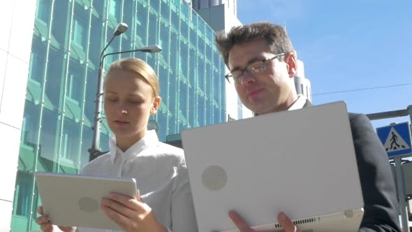 Cover Image for Busy Businesspeople With Electronics In The City