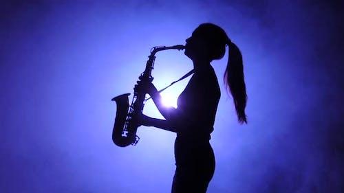 Jazz durchgeführt von Musiker Mädchen spielen Saxophon, Silhouette, Zeitlupe