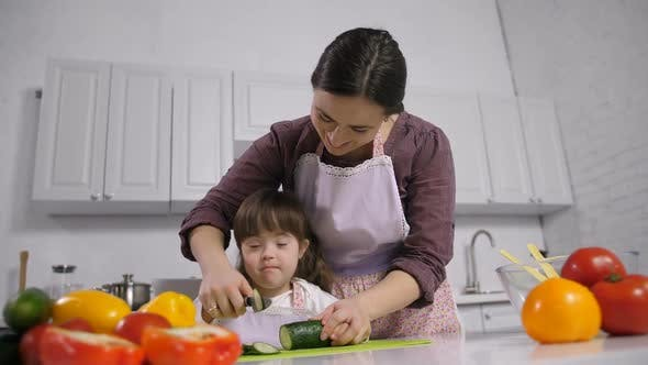 Thumbnail for Handicapped Down Syndrome Child with Mother Cooking