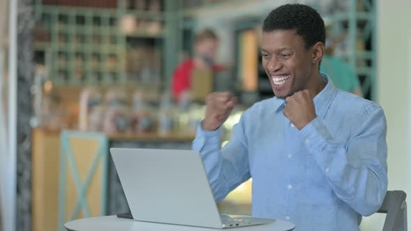 Excited African Businessman Celebrating Success on Laptop in Cafe