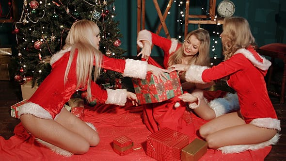 Thumbnail for Girls In Santa Claus Costumes Preparing A Gifts