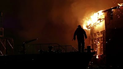 House On Fire. Conflagration. Fireman Fights Fire.