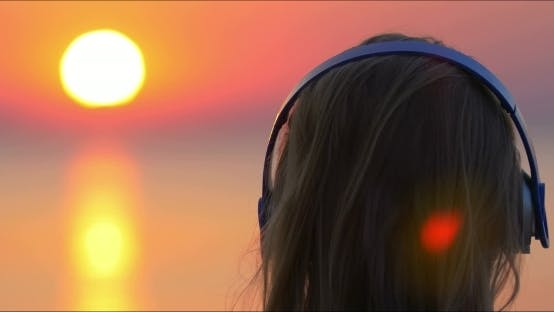 Thumbnail for Girl Listening To Music And Looking At Sunset