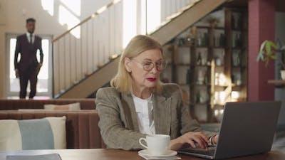 Senior Businesswoman Using Laptop in Restaurant