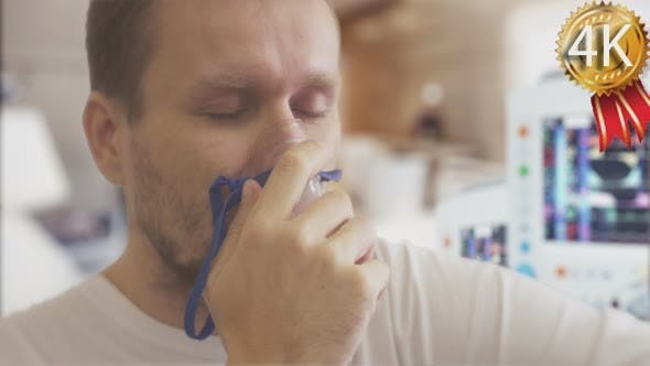 Thumbnail for Young Man is Caughing Breathing Through Nebulizer