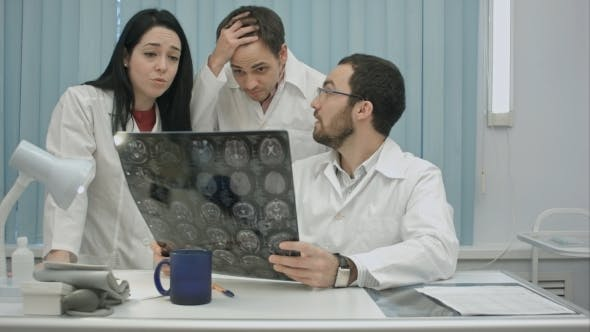 Thumbnail for Trio Of Young Afraid Physicians Checking Patient's