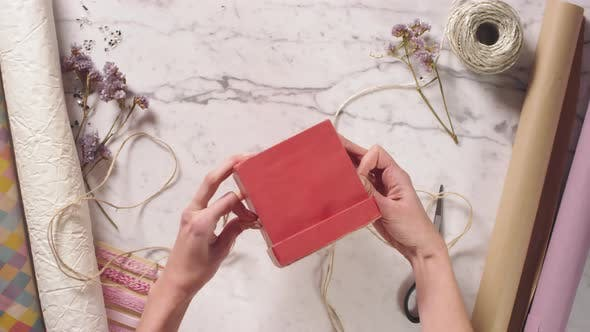 Thumbnail for Hands of Woman Decorating Red Gift Box with Jute Rope