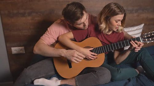 Beautiful Young Man Teaches His Girlfriend To Play the Guitar While Sitting at Home During a Period