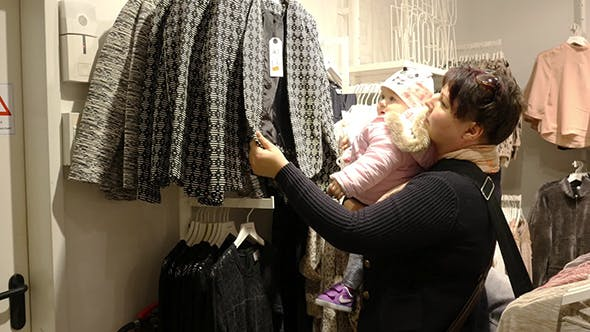 Thumbnail for Woman With Baby Choosing Clothes During Shopping
