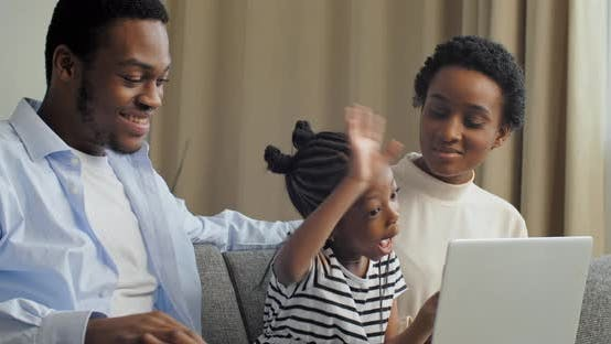 Side View of Parents with Little Daughter Looking at Laptop Listening To Lesson Communicating with