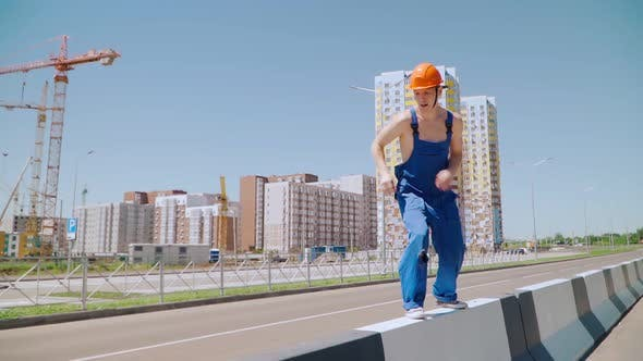 Happy Caucasian Man Builder in Hard Hat Dancing. Worker Funny Moves Background Construction Site.