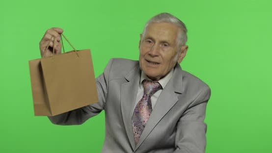 Thumbnail for Elderly Man with Shopping Bag. Looks Into the Camera and Stretches the Gift