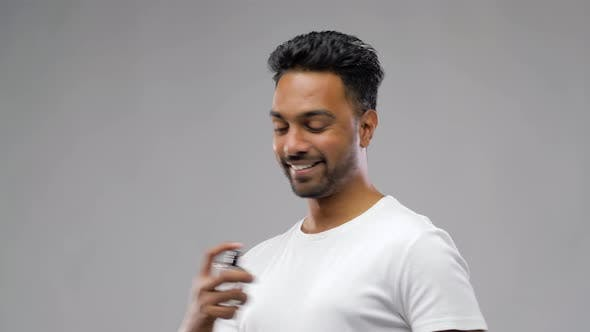 Thumbnail for Happy Indian Man with Perfume Over Gray Background